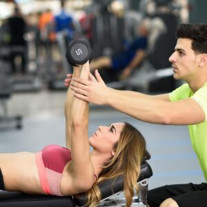 Personal trainer helping a young woman lift weights while working out in a gym