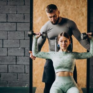 Woman doing workout at the gym with trainer